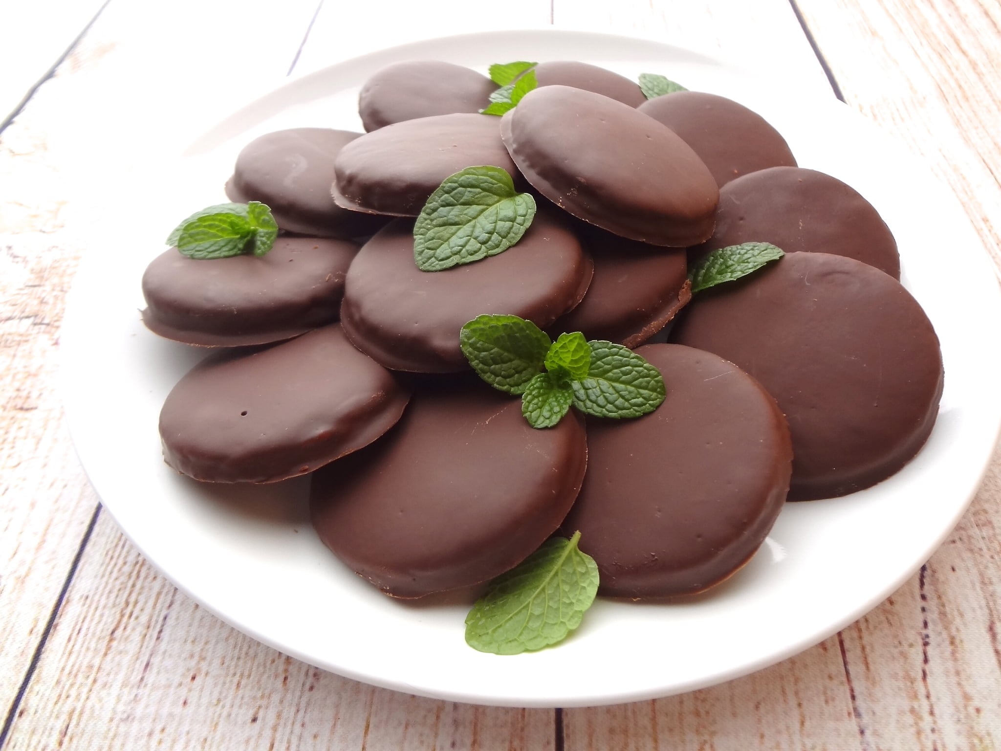 Vegan Thin Mints on a white plate and white wood with mint leaves.