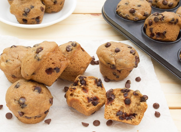 Mini Vegan Chocolate Chip Muffins on parchment paper with one broke open.