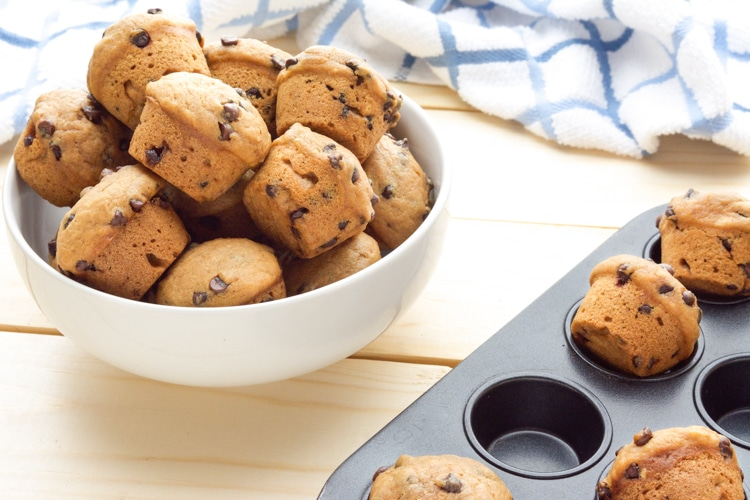 A muffin pan and white bowl with mini Vegan Chocolate Chip Muffins.