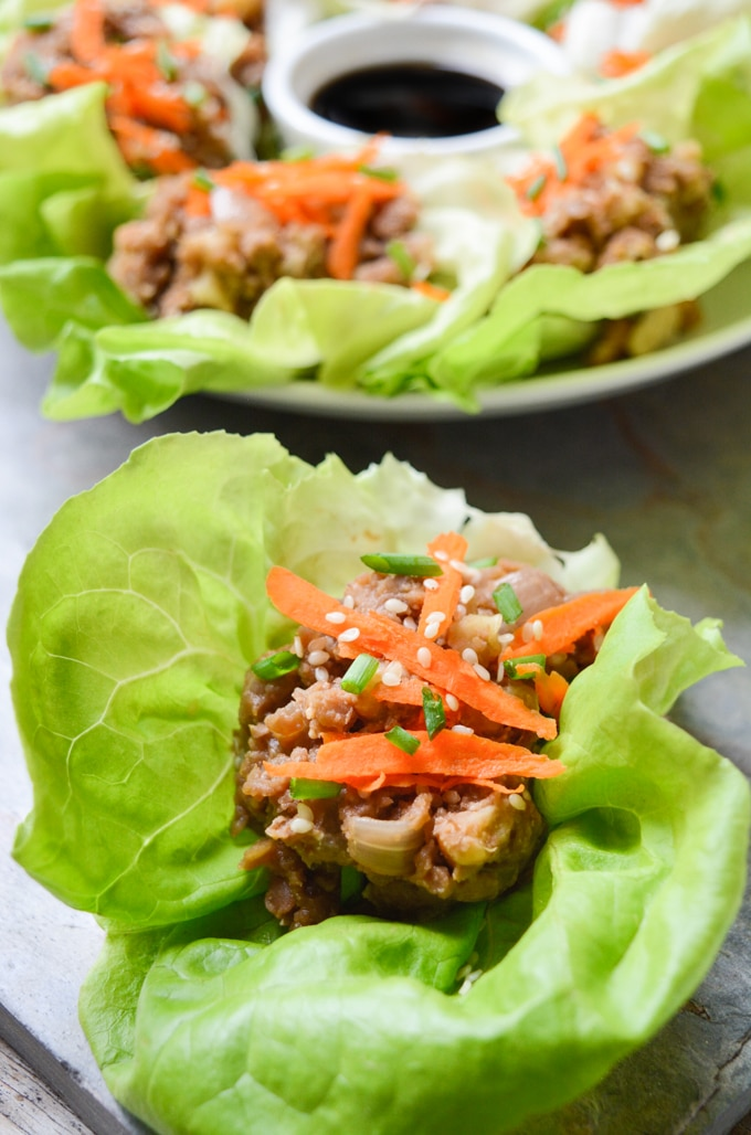 Vegan Lettuce Wraps-- Close up of the butter leaf lettuce filled with a lentil walnut mix, then topped with an Asian inspired sauce, grated carrots, green onions and toasted sesame seeds. More plated vegan lettuce wraps are in the back. They're served with an extra side of sauce in the middle of the plate.