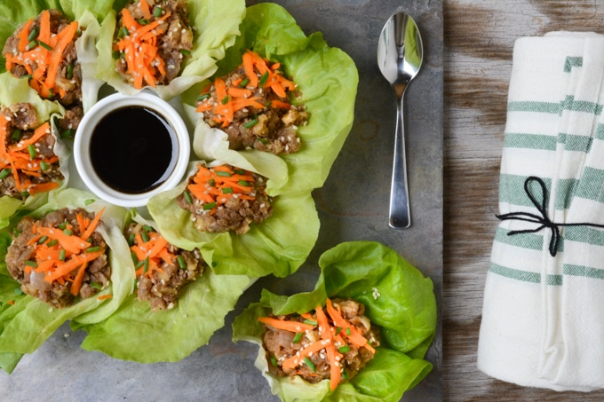 Top view of vegan lettuce wraps. Butter lettuce leaves filled with a 'umami' lentil-walnut mix. Served with a side of Asian-inspired sauce.