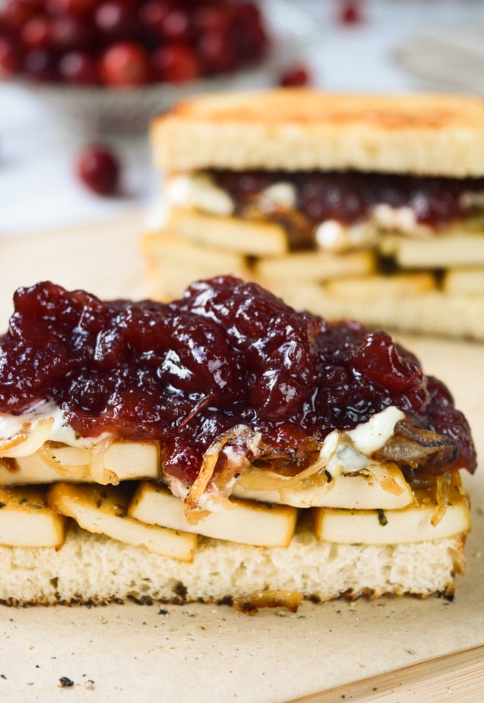 Vegan Holiday Sandwich-- Sourdough bread piled with herb tofu, caramelized onions, savory herb dressing and cranberry sauce.