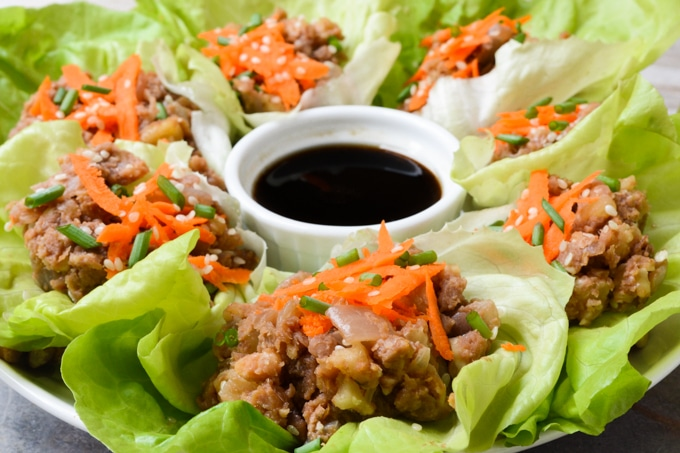 Vegan Lettuce Wraps-- Plated butter lettuce leaves filled with a lentil walnut mix, then topped with an Asian inspired sauce, grated carrots, green onions and toasted sesame seeds. Served with an extra side of sauce on the plate.