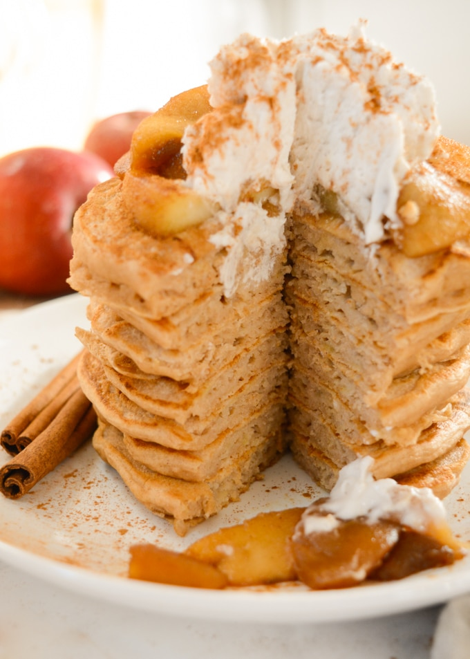 Stack of Apple Cinnamon Pancakes with a wedge cut out and a view inside the pancakes.