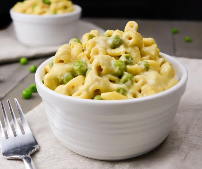 Creamy vegan mac and cheese with peas in a white bowl with a fork next to the bowl.