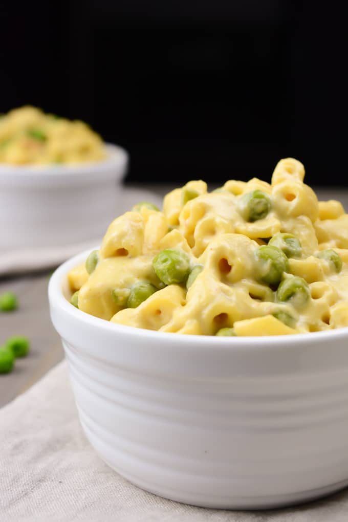 Creamy vegan mac and cheese with peas in a white bowl set on a napkin.